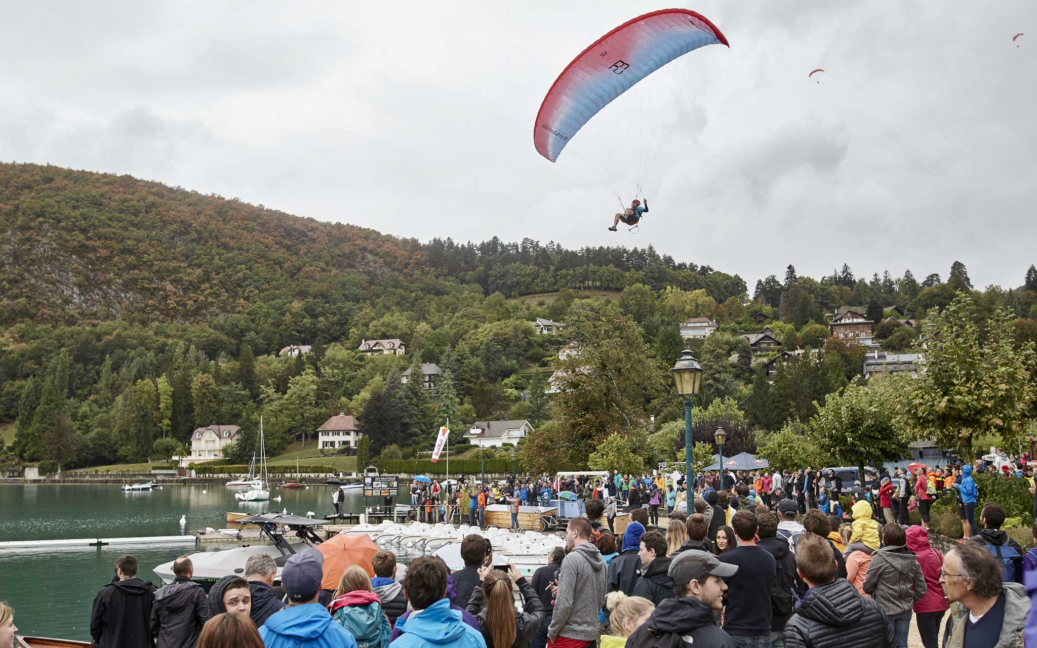 Participants paraglide above the crowd at the Red Bull Elements in Talloires, France on September 17th, 2016. // Tim Lloyd / Red Bull Content Pool // P-20160917-01655 // Usage for editorial use only // Please go to www.redbullcontentpool.com for further information. //